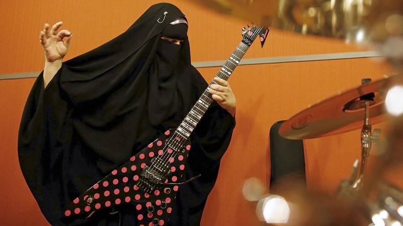 """Gisele Marie, a Muslim woman and professional heavy metal musician, plays her Gibson Flying V electric guitar during a rehearsal at a studio in Sao Paulo January 27, 2015. Based in Sao Paulo, Marie, 42, is the granddaughter of German Catholics, and converted to Islam several months after her father passed away in 2009. Marie, who wears the Burka, has been fronting her brothers' heavy metal band """"Spectrus"""" since 2012. """"People do not expect to see a Muslim woman who uses a Burqa, practices the religion properly and is a professional guitarist who plays in a Heavy Metal band, so many people are shocked by it. But other people are curious and find it interesting, and others think that it is cool, but definitely, many people are shocked,"""" said Marie. Picture taken January 27, 2015. REUTERS/Nacho Doce"""